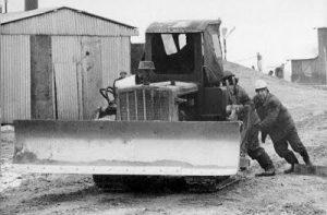 """Fotografia z serii """"PRL"""", przedstawiająca dwóch mężczyzn pchających traktor"""