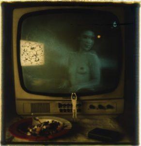 Celowo nieostre zdjęcie przedstawiające stolik z telewizorem, talerzem z niedokończoną potrawą i figurką; w telewizorze odbija się roznegliżowana kobieta, widoczna od pasa w górę
